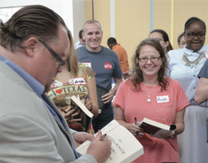 Author and clinical social worker Christian Moore signing books for faculty and staff at the district-wide summer convocation.