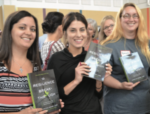 UT-UCS faculty smile for the camera as they wait in line to have their books signed.
