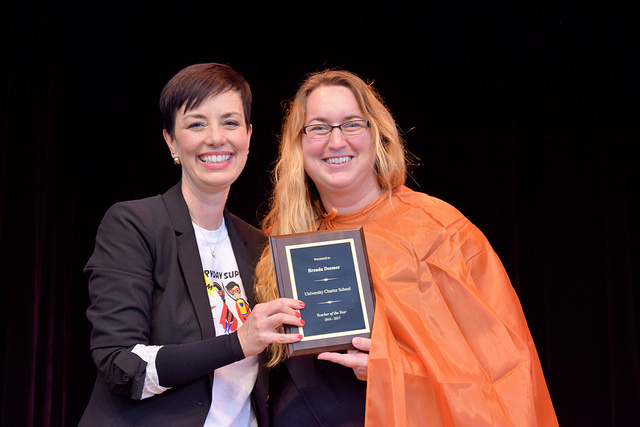 Brenda Deemer (right), receives her Teacher of the Year Award at the superhero-themed summer convocation ceremony