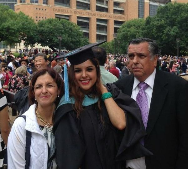 Graduate in cap and gown with parents at commencement
